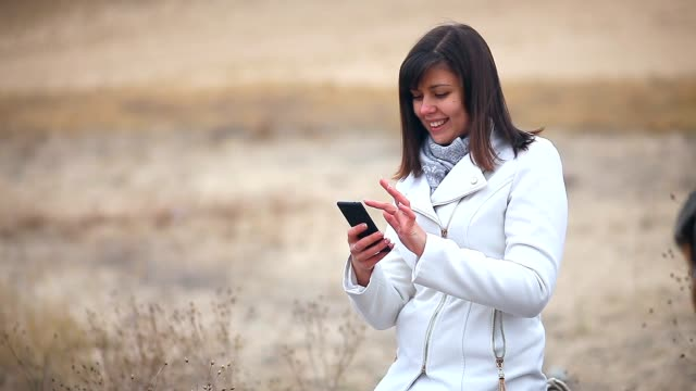Woman searching the internet smart phone social media nature autumn video
