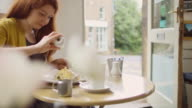 Woman Seasoning Meal in Sunlit Cafe video
