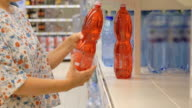 Woman selecting cooling beverages at store video