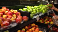 Woman selecting fresh green apples in grocery store video