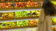 Woman selecting fresh red apples in grocery store produce department and putting it in plastic bag. Young pretty girl is choosing apples in supermarket and putting them into shop basket. Close up video
