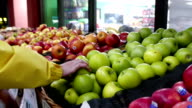 Woman selecting green apple in grocery store video