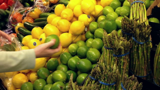 Woman selecting lime in grocery store video