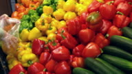 Woman selecting red and yellow peppers in grocery store video