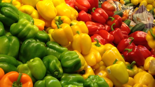 Woman selecting yellow peppers in grocery store video