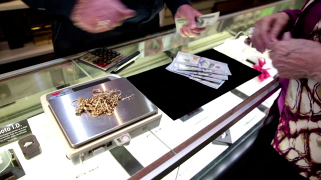 Woman selling her old gold jewelry to jeweler for cash video