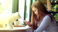 woman sending message on smart phone in cafe video