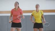 Woman serving in playing doubles indoor badminton video