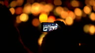 Woman Shooting water lanterns with a mobile phone video