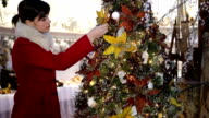 woman shopping christmas decorations for tree in market store video