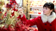 woman shopping christmas decorations in market store video