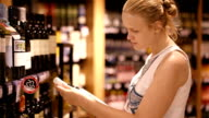 Woman shopping for alcohol in a bottle store video