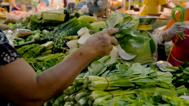 woman shopping for fresh vegetables at market. video