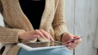 Woman shopping online at digital tablet with credit card video