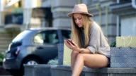 Woman shopping online using mobile phone outdoor video