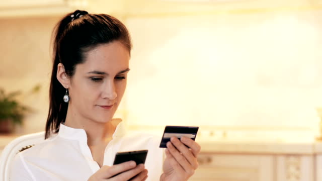 Woman shopping online with mobile phone at home video