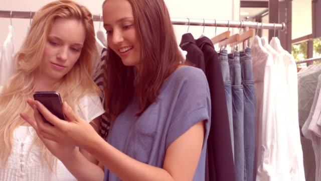 Woman showing her friend a dress video