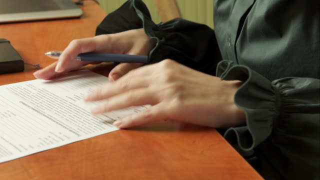 Woman signs a document video