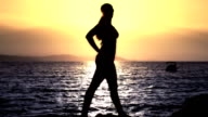 Woman silhouette on the beach at sunset video