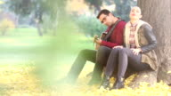 Woman singing and man playing guitar while sitting on a tree in park video
