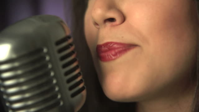 Woman singing into microphone, close up video