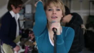 Woman sings with band in garage video