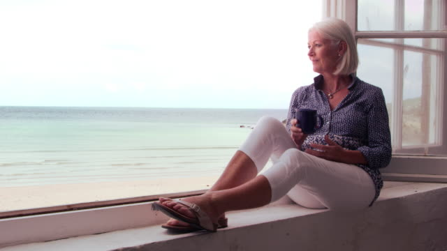 Woman Sits At Window And Looking At Beach View Shot On R3D video