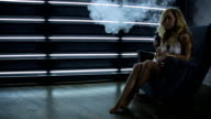 Woman sits in armchair, smokes electronic cigarette and exhales volumes of vapor in front of her video