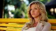 Woman sits in park broken relationships, problem, depression video