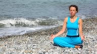 Woman sits in pose of lotus on beach video
