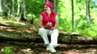 Woman sits on a fallen tree in the forest listens to music and sings a song video