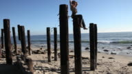 Woman sits on a wooden post and watching the sea video