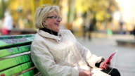 Woman sits on the bench in the city park and communicates via red smartphone video