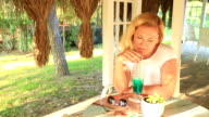 Woman sitting at the summer cafe and drinking cocktail video