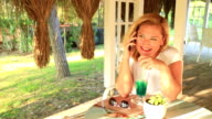 Woman sitting at the summer cafe and talking on the phone video
