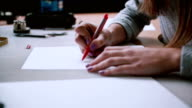 Woman sitting at the table, holding pencil and drawing layout on paper. Erase in sketch. Slider left, side view. 4K video