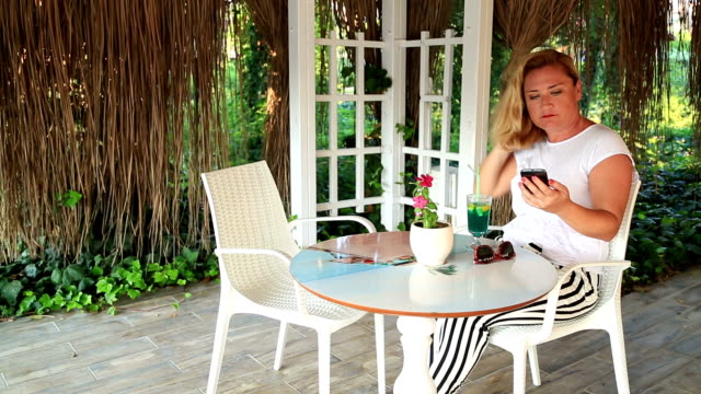 Woman sitting at the table in summer cafe witn a phone and waiting to somebody video