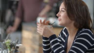 Woman sitting in a cafe, drinking with a straw, close up video