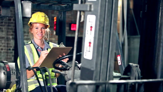 Woman sitting in forklift looking at clipboard video