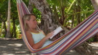 Woman sitting in hammock reading book video