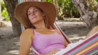 Woman sitting in hammock relaxing video