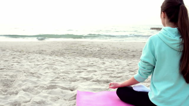 Woman sitting in yoga lotus pose on the beach video