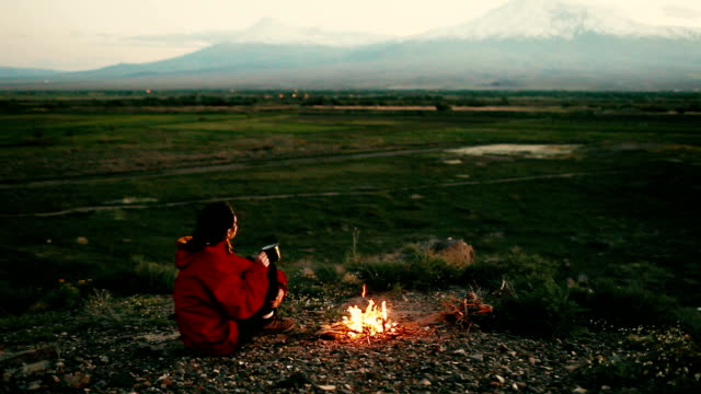 Woman sitting near the campfire near  Ararat video