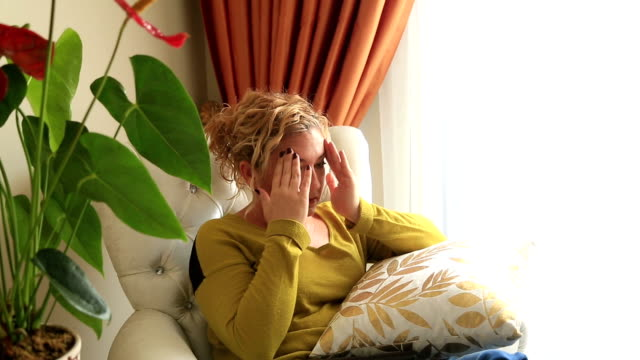 Woman sitting on a couch and having headache video