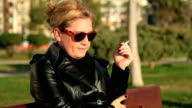 Woman sitting on a park bench and smoking cigarette video