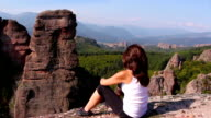 Woman sitting on a rock and admiring the beautiful Belogradchik valley video