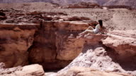 Woman sitting on a rock in the desert video