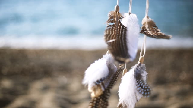 Woman sitting on beach sand with Dreamcatcher video
