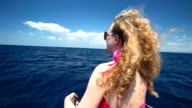Woman sitting on bow of sailing boat enjoying view of sea video