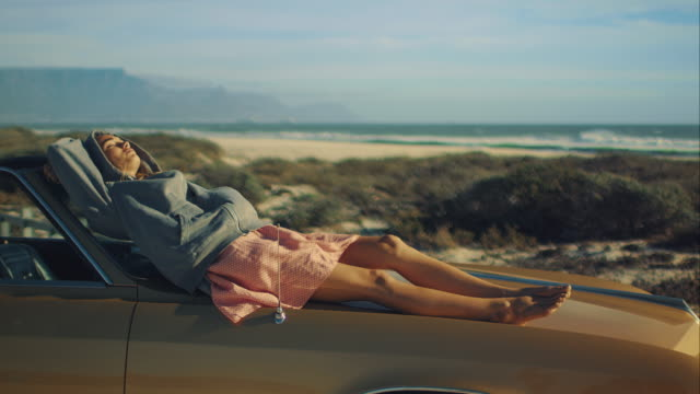 Woman sitting on car at the beach video